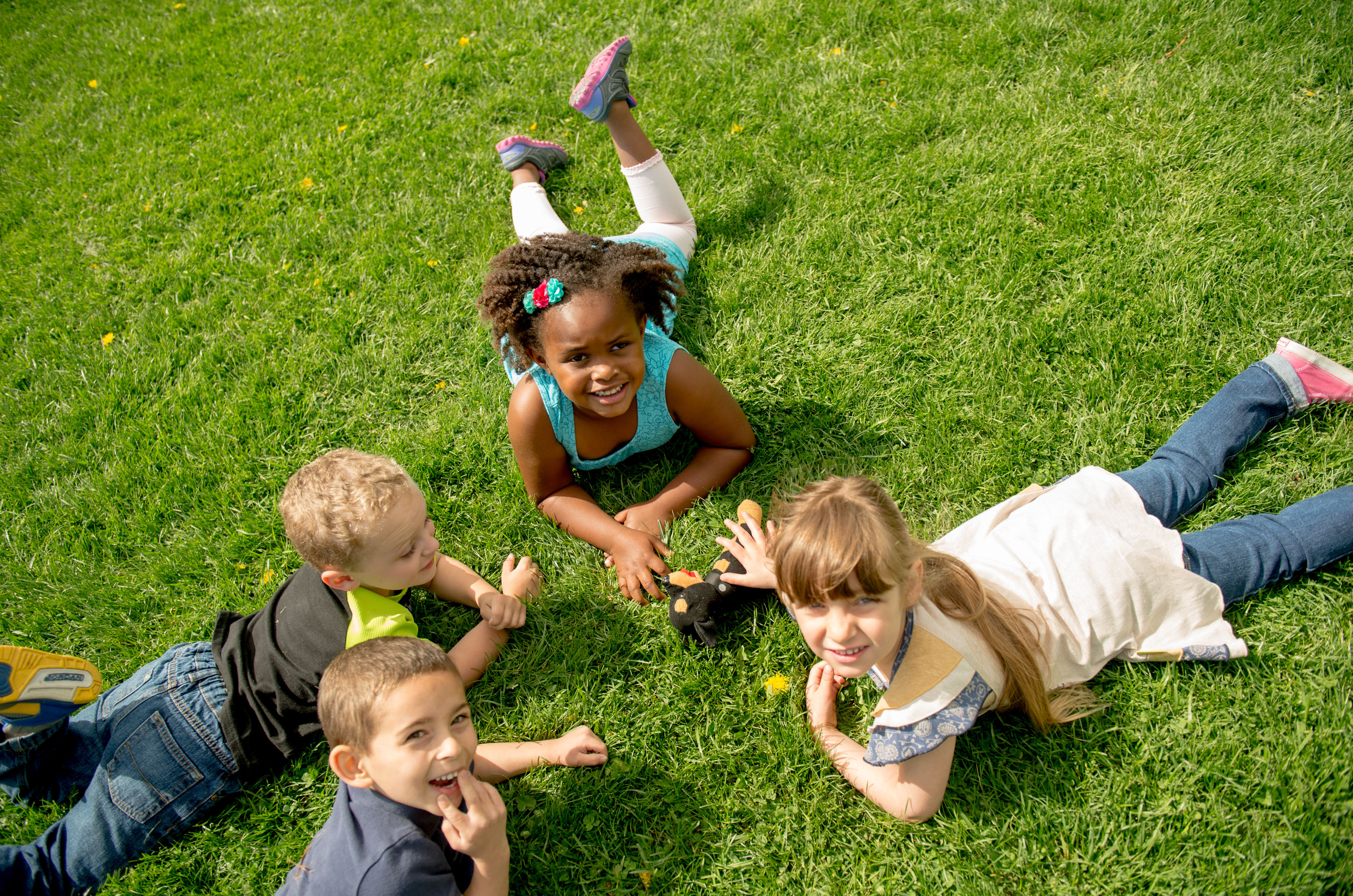 circle of children lying on the grass
