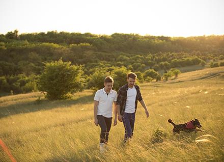 Two men walking on hillside with dog