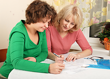 Older woman assists younger woman with important papers