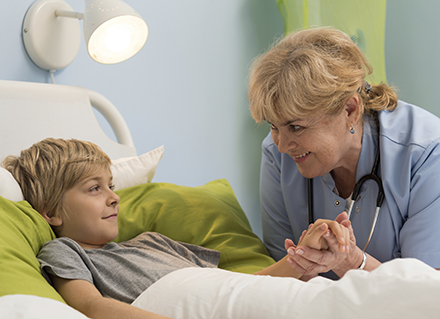 Clinician holding young boys hand in hosptial bed.