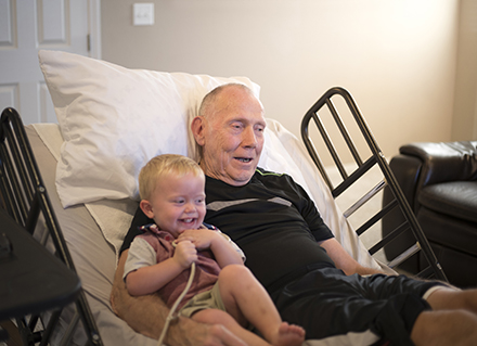 Grandfather in hospice bed with smiling toddler grandson.