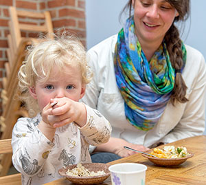toddler with mom and rice bowl