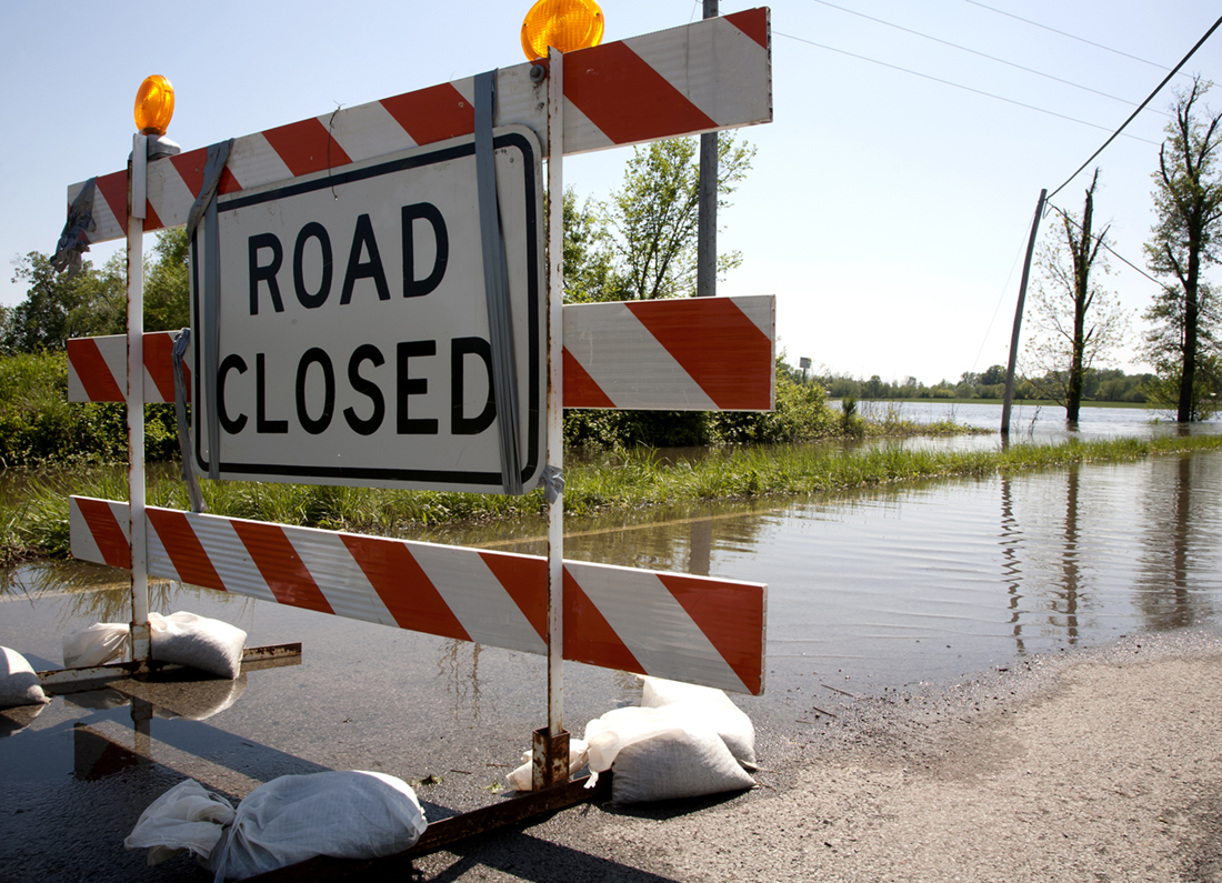 road closed sign in front of flooded road