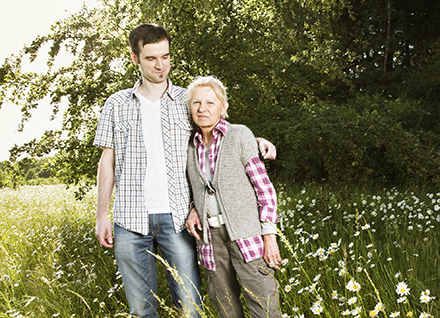 Young man and older woman standing in field of daises.