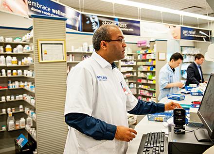 Pharmacist filling prescription at computer.