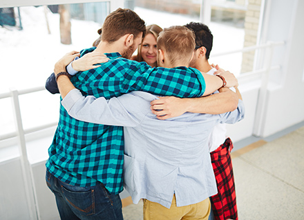 Group of young adults in circle with arms around each other.