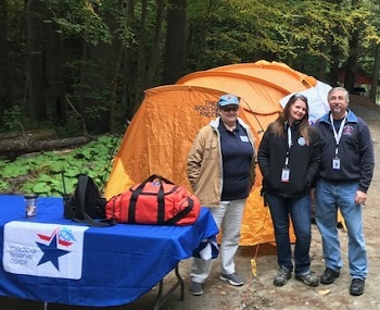 3 volunteers in front of tent in woods