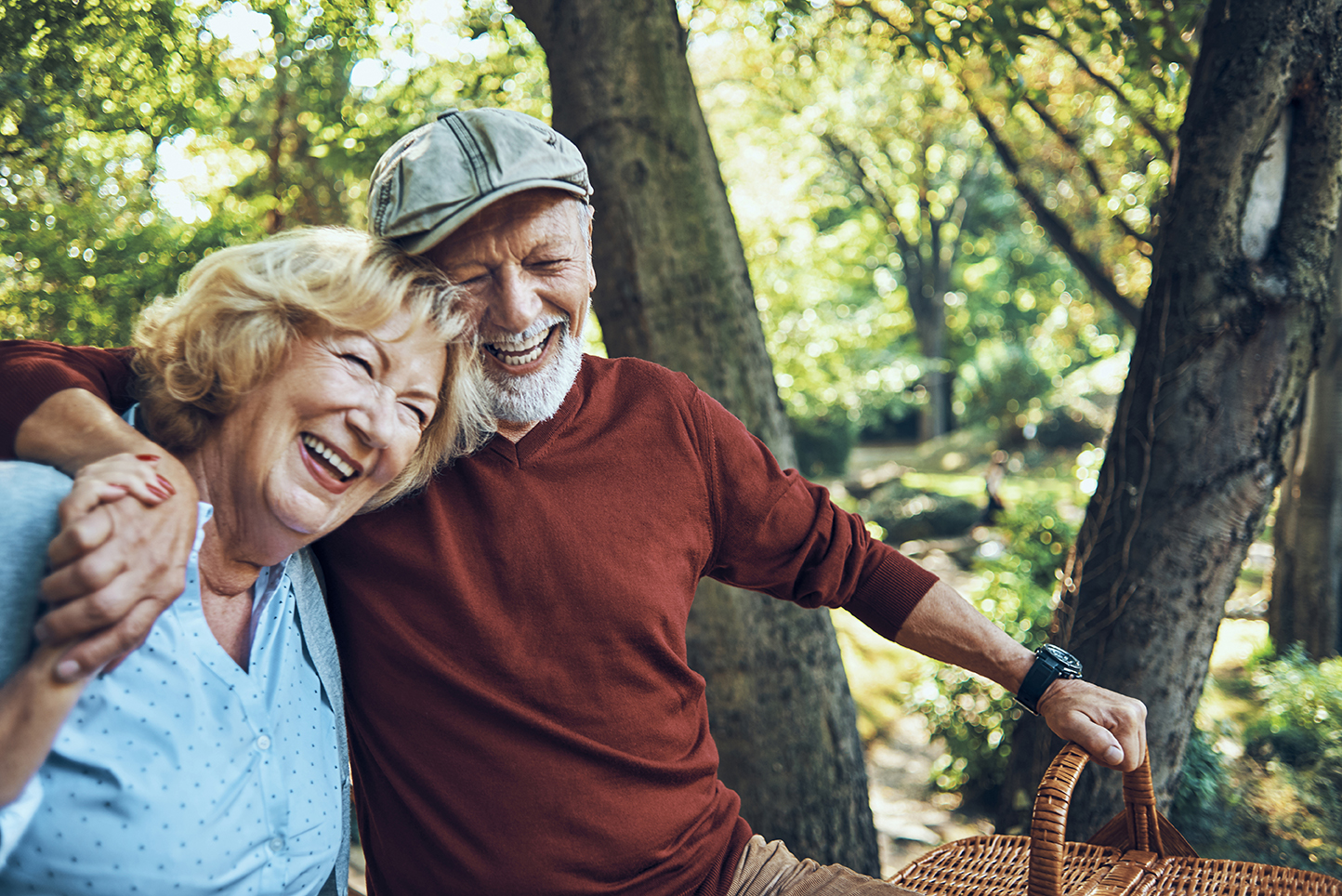 Older man and woman smiling with picnic basket