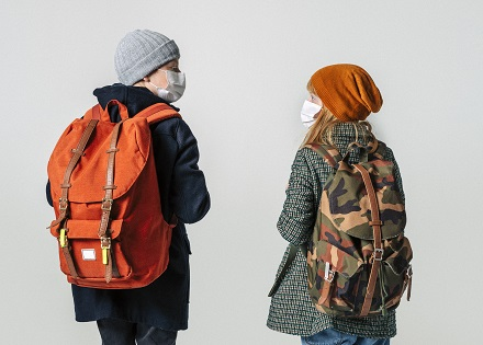 two kids in masks, coats and backpacks