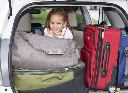girl and luggage in car