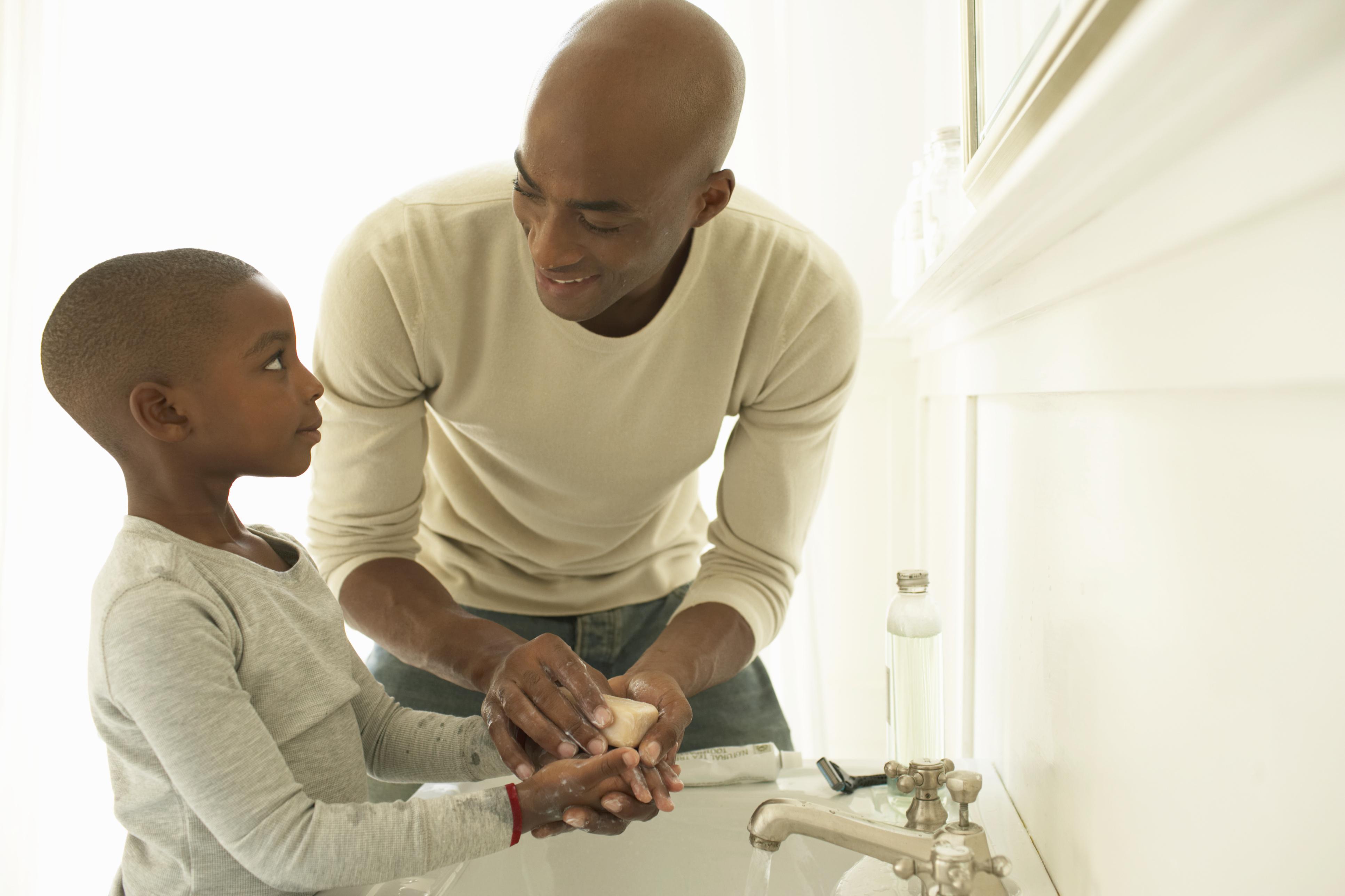 man and boy washing hands
