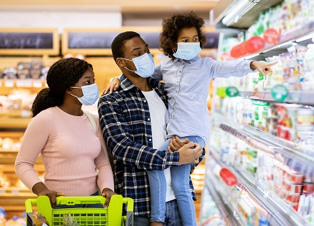 family wearing masks while grocery shopping