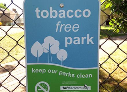 "sign ""tobacco free park"" on fence"