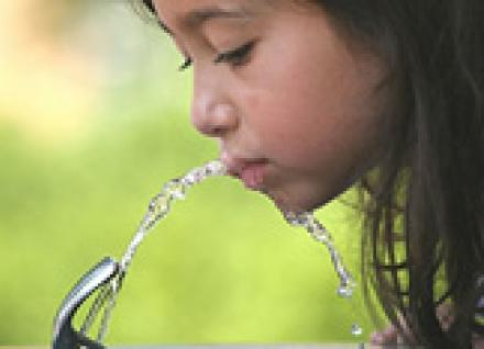 Girl drinks from water fountain