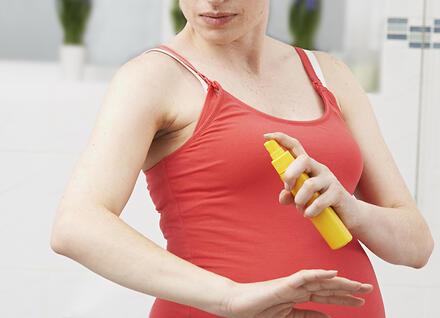 pregnant woman applying tick repellent
