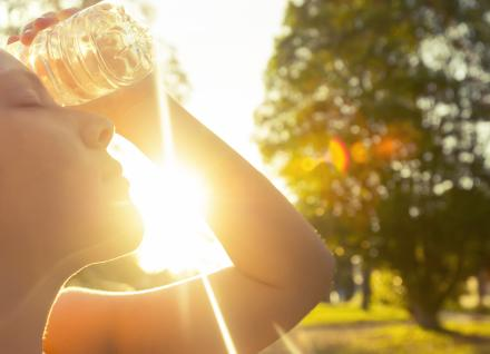 woman holding a water bottle to her head on a hot, sunny day