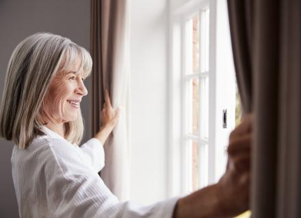 women opening window in home