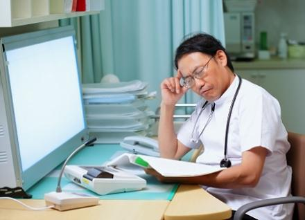 health professional in front of screen looking at journal