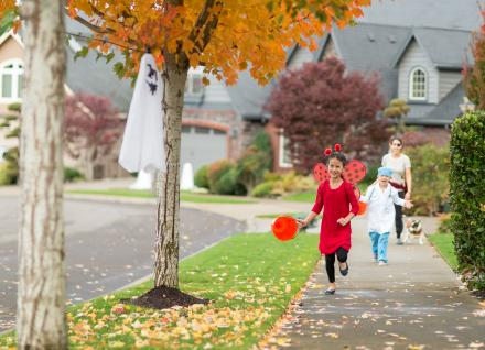 Children in Halloween costumes running on sidewalk