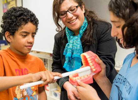 woman showing students model teeth