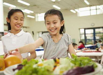 girl reaching for healthy food in school cafeteria