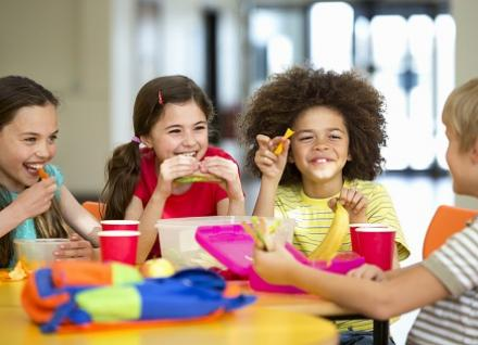 children smiling at school lunch