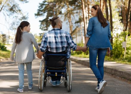 three people on walking path, including a child, man in a wheelchair and woman, holding hands