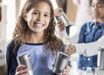 child holding unlabelled aluminum cans, bottled water and others in background, preparing for emergency