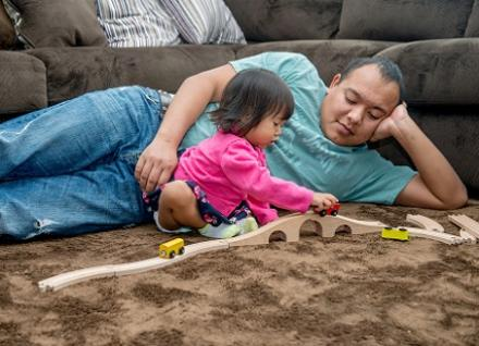 man watchng toddler play with toy train tracks