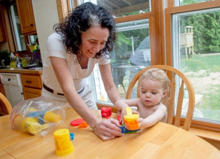 woman helping toddler with playdoh