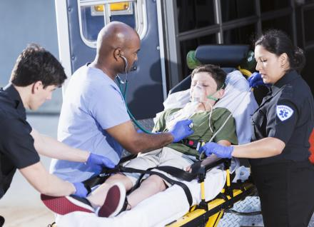 Doctor and paramedics helping boy lying on a stretcher outside an ambulance.