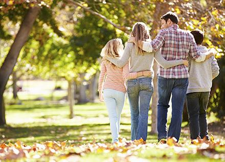 Family of four walking away in a wooded park during fall.