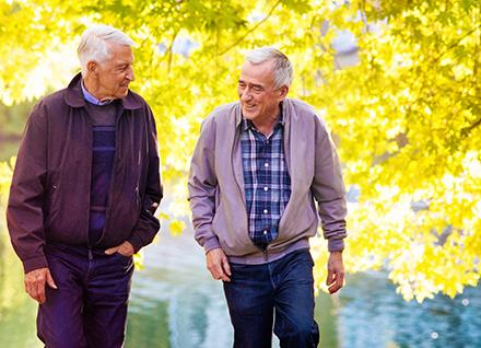Senior men walking in fall leaves