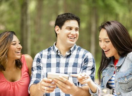 three young adults looking at phone