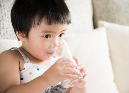 toddler drinking water from glass