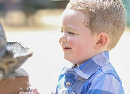 boy drinking at outdoor fountain