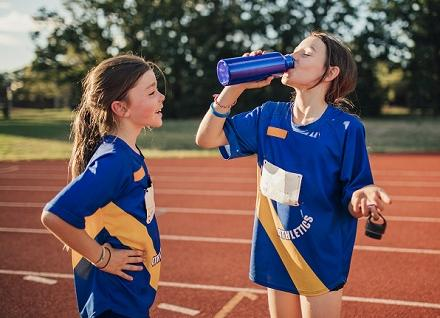 girls on track drinking water from bottle