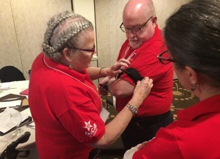 three volunteers practicing applying tourniquet