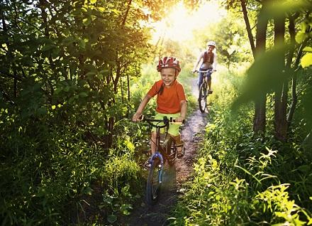 two children biking in woods