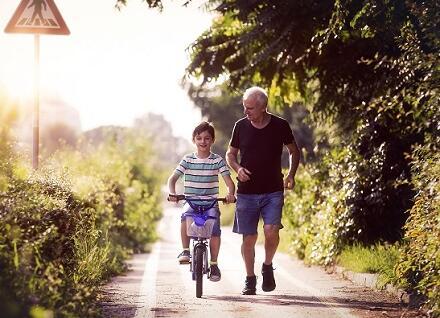 boy biking with man running