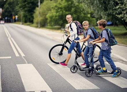 kids on scooters crossing road