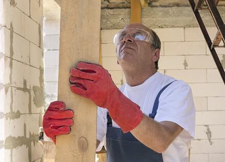 worker in gloves holding board