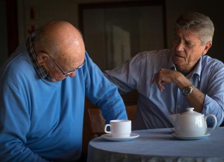 Two men talking at table with teapot and mug