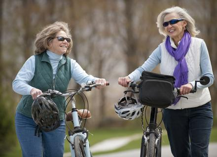 Two older women walking their bikes together
