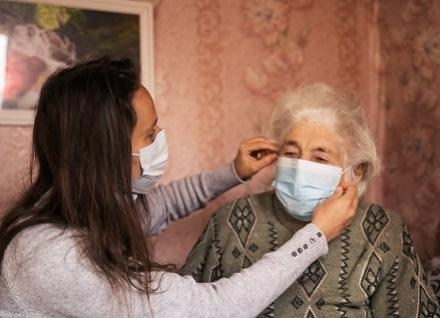 person helping older woman put mask on