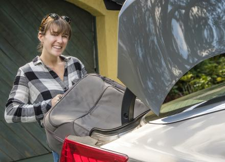 woman loading suitcase into car