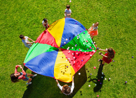 Kids playing with a parachute outdoors on a sunny summer day