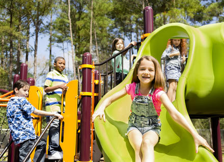 Happy young children on a playground on a sunny day