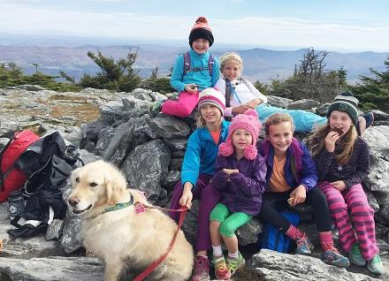 children and dog on mountaintop