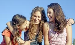 three teen girls smiling